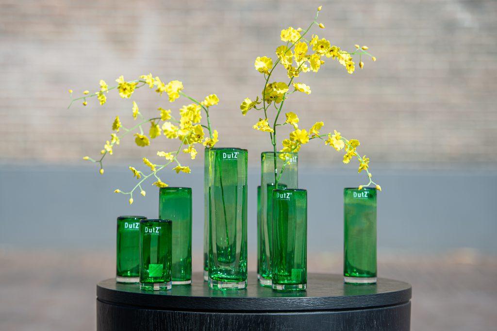 Bladgroene cilinders op een rond houten tafeltje. Een aantal cilinders zijn gevuld met gele bloemen