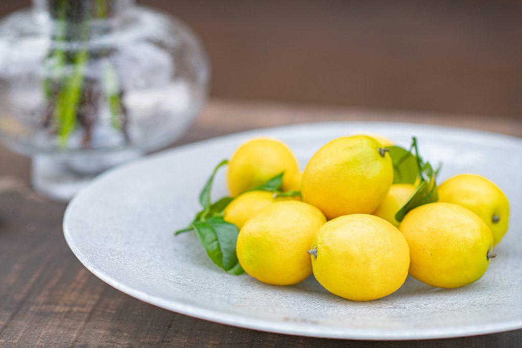 Plate met citroenen in de kleur wit. Op de achtergrond een Modest vaas in helder glas