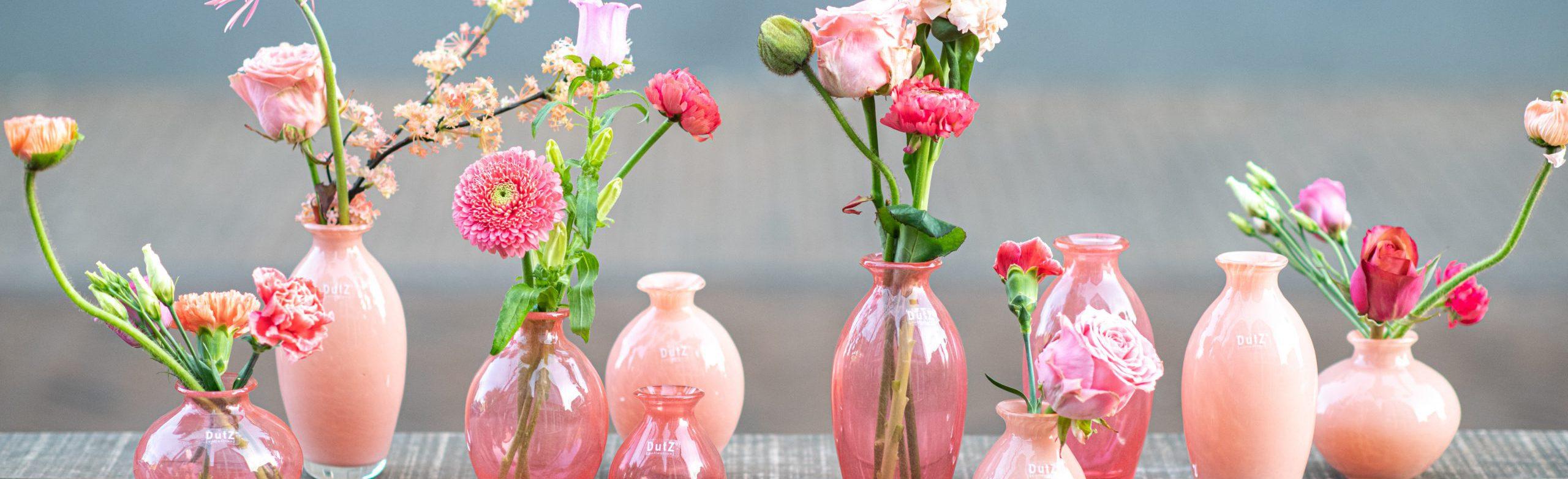 DutZ vaasjes uit de serie Nadiel in verschillende roze tinten. Alle vaasjes zijn gevuld met roze bloemen. De vaasjes staan op een rij naast elkaar op een tafel