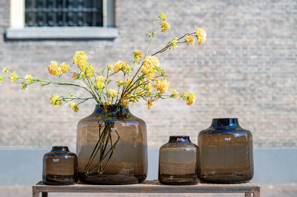 Vier Tisza vazen in de kleur smoky brown. De vazen hebben alle vier een andere maat In de grootste staan mooie oranje takken