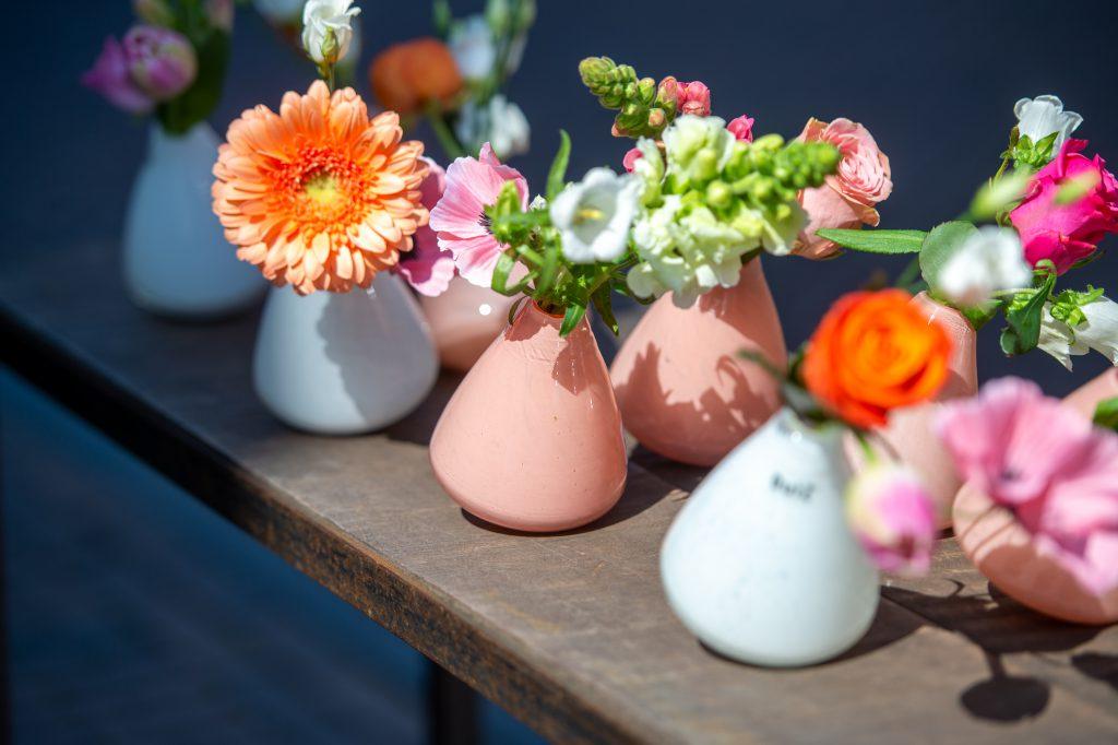 Tuimelvaasjes in wit en in apricot gevuld met bloemen