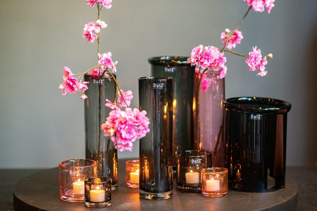 Cilinders in smoke en apricot. Varierend in hoogte. Gevuld met kaarsen en bloesemtakken